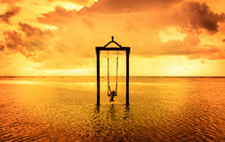 A girl on a swing over the sea at sunset in bali,indonesia 7 Stock Images