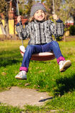 Girl in swing at playground Stock Photography