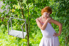 The girl and a swing. The girl plays near a swing Royalty Free Stock Images