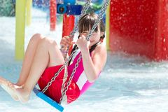 Girl on swing in pool Stock Image