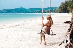 Girl on swing. Girl sitting on the swing on the tropical beach, paradise island Royalty Free Stock Photo