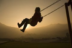 Girl on Swing at sunset Stock Image