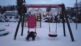 Girl on a swing tire covered in a deep snow. Little girl having fun on a tire swing on the children playground covered in a layer of deep snow, Tromso, Norway stock video footage