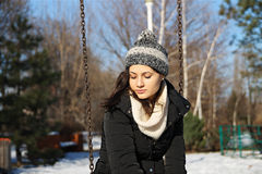 Girl on swing in winter. Portrait of a auburn girl on a swing in winter Royalty Free Stock Photos