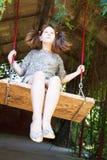 Girl swing on wooden board in backyard Stock Photos