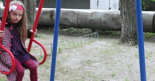 Girl on a swing in the working area. In the working area of the depressed girl in a coat and a bow ride on a swing stock video footage