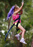 Girl Swinger. A young girl swinging from a cable at a park Stock Image