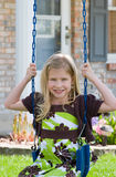 Girl Swinging. Little Girl Swinging in Front of Her House Stock Photography