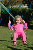 Girl swinging. A full body of a beautiful blond caucasian white girl child with happy laughing expression in the pretty face dressed in pink clothes sitting on a royalty free stock images
