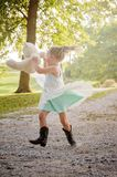 Girl swinging bear in the air Stock Photo