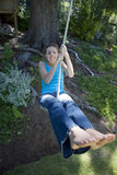 Girl (8-10) swinging on garden rope swing, smiling, front view, portrait Stock Photo
