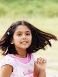Girl with swinging hair. A young girl in swinging her hair around, wearing a pink dress, and hair clips in her hair Stock Photo