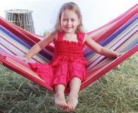 Girl swinging on a hammock in the hay Stock Photos