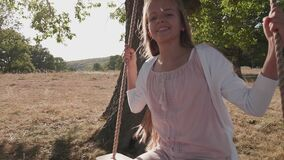 Girl swinging with a large smile on rope swing