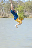 Girl swinging over river Royalty Free Stock Image