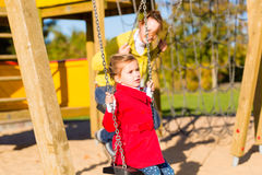 Girl swinging on play area or court Royalty Free Stock Images