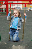 Girl swinging in a playground Royalty Free Stock Images