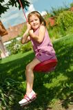 Girl swinging on seesaw Stock Photo