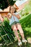 Girl swinging on seesaw Stock Photos