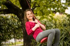 Girl swinging on seesaw Stock Photo