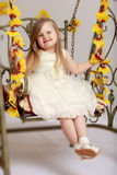 Girl swinging on a swing. Adorable little round-faced girl with long, blonde hair below the shoulders, little Princess in a white dress. Girl swinging on a swing Royalty Free Stock Photo