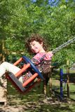 Girl swinging on swing happy in trees outdoor Stock Photo