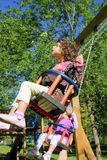 Girl swinging on swing happy in trees outdoor Stock Photography
