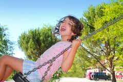 Girl swinging swing in outdoor park nature Royalty Free Stock Image