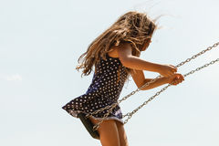 Girl swinging on swing-set. Royalty Free Stock Photography