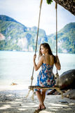 Girl swinging on a tropical island Stock Images