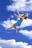 Girl on swings. Merry girl on swings in sky Royalty Free Stock Photography