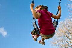 Girl swings into sky. Girl swings high into a blue sky with copyspace Stock Images
