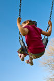 Girl swings into sky. Girl swings high into a blue sky vertical Royalty Free Stock Images