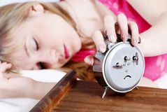 The girl switching off alarm clock Stock Images