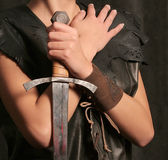 Girl with sword. Standing in self defense. Soft skin contrasts cold metal Royalty Free Stock Images