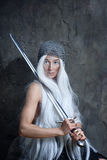 Girl with sword. Androgyny girl in armor with a sword and looking at the camera Royalty Free Stock Image