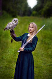 Girl with sword holding an owl on her arm Royalty Free Stock Images