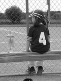 Girl T-Ball Player. A redhaired little girl t-ball player waiting on the bench with her sports bottle Royalty Free Stock Photos