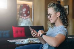 Girl in t-shirt is chatting, blogging, checking email.Student learning, studying. Online marketing, education, e. Side view. Young businesswoman in glasses sits royalty free stock photography