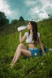Girl in a t-shirt drinking milk. Royalty Free Stock Photos