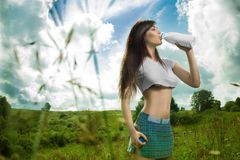 Girl in a t-shirt drinking milk. Royalty Free Stock Photo