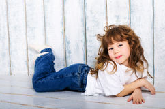 Girl in a T-shirt and jeans. Little girl lying on floor Royalty Free Stock Images