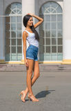 Girl in a t-shirt and shorts in front of a building with columns Royalty Free Stock Photo