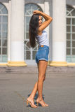 Girl in a t-shirt and shorts in front of a building with columns Stock Photography