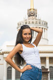Girl in a t-shirt and shorts in front of a building with columns Stock Photo