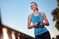 The girl in a t-shirt and shorts is standing by the lake with a smartphone and headphones after jogging. Stock Photos