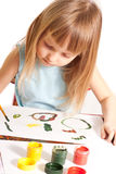 Girl at the table. Little girl sitting at the table and painting Royalty Free Stock Photo