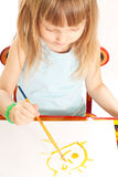 Girl at the table. Little girl sitting at the table and painting Royalty Free Stock Photography