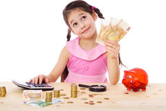 Girl at the table counts money Royalty Free Stock Images