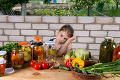Girl at Table Covered by Vegetables and Preserves Royalty Free Stock Photo